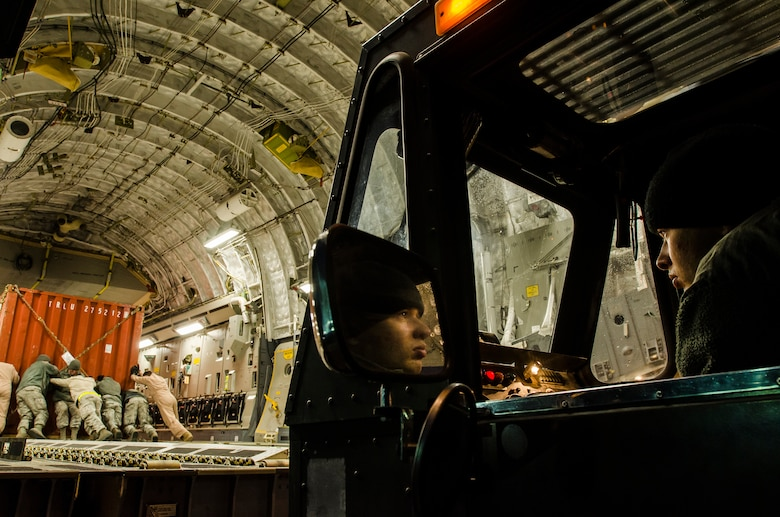 Senior Airman Seth Allen operates a cargo loader as Airmen move equipment in place on a C-17 Globemaster III March 14, 2014, at Transit Center at Manas, Kyrgyzstan. Allen and other Airmen loaded outbound cargo in preparation for the base closure, scheduled for July 10. Allen is a 376th Expeditionary Logistics Readiness Squadron ramp service specialist. (U.S. Air Force photo/Senior Airmen Ross Alexander Whitley)
