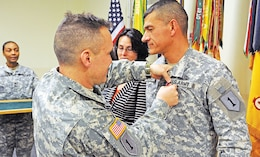 Col. John Reynolds III, commander, 1st ABCT, pins the Legion of Merit on Command Sgt. Maj. Mark Kiefer, outgoing senior NCO, 1st ABCT, during a Jan. 8, 2014 ceremony at Fort Riley. Kiefer was joined by his wife, Patricia, who received the Lady Victory award.