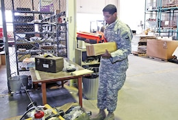 Spc. Corey Fisher, automated logistic specialist, 1st Support Maint. Co., 541st CSSB, picks BRO-MRT order items Feb. 24 at Fort Riley. Units utilizing the BRO-MRT are helping save the Army millions of dollars each year.