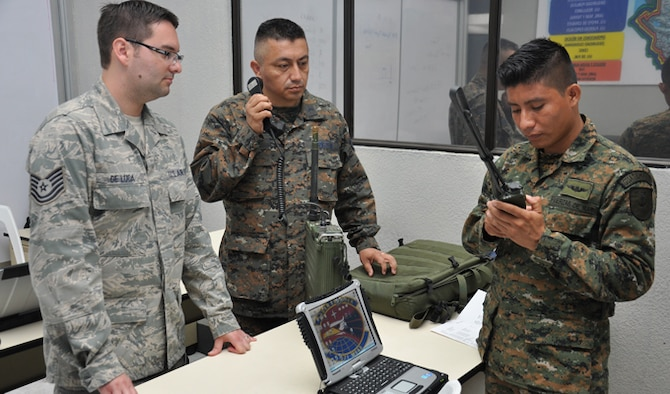 Tech. Sgt. Brian De Luca and Guatemalan air force Cabo Especialista Luis Alberto Gonzalez Prado watch Guatemalan navy Marinero Segundo, Melvin Ivan Garcia Alvarado, perform a radio check during classroom instruction Mar. 11, 2014, at La Aurora air base, Guatemala. Seminars conducted by the 571st Mobility Support Advisory Squadron highlighted aircraft maintenance, aircraft security, radio communications and intelligence. De Luca is a 571st MSAS communications air adviser. (U.S. Air Force photo/Staff Sgt. Christopher Carranza)