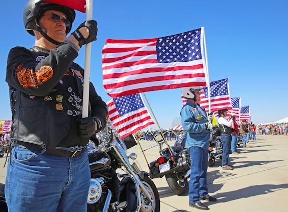Larry Buthmann, a former service member and a native of Estherville, Iowa, (left), holds an American flag firmly as part of the Patriot Guard Riders opening ceremony for the 52nd Annual Yuma Airshow at Marine Corps Air Station Yuma, Ariz., March 15. The non-profit veterans support organization filed out on motorcycles and presented a flag line in honor of fallen veterans and active-duty service members.