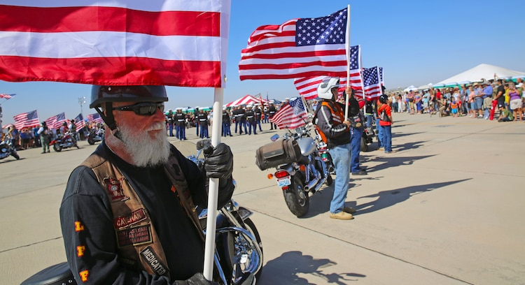 Reg Amell (left), who retired after a combined 28 years of service in the United States Air Force, U.S. Army, U.S. Marine Corps and U.S. Merchant Marines, stands his post at Marine Corps Air Station Yuma, Ariz., as part of the Patriot Guard Riders opening ceremony for the  52nd Annual Yuma Airshow, March 15. The non-profit veterans support organization filed out and presented a flag line in honor of fallen veterans and active-duty service members. (Photo by Cpl. Uriel Avendano)