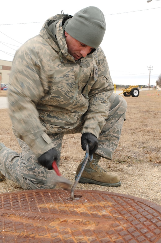 Senior Master Sgt. Jose Franco, from the 253rd Combat Communications Squadron, chips ice away from a manhole cover before gathering real-world data on the infrastructure of Otis Air National Guard Base during a GeoBase class on January 21, 2014. (National Guard photo by Master Sgt. Aaron Smith/Released)
