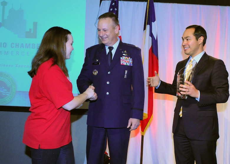 Col. William Poirier, 67th Cyberspace Wing commander, and San Antonio Mayor Julian Castro shake hands with a member of a San Antonio CyberPatriot team during the Mayor's Cyber Cup in San Antonio March 1. CyberPatriot is a national cyber defense competition created by the Air Force Association to encourage students toward careers in cybersecurity. (Courtesy photo)