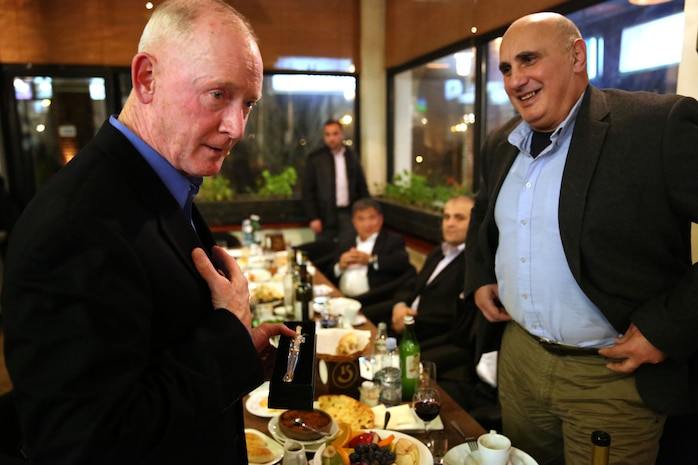 Lieutenant Gen. Richard Tryon, commander of U.S. Marine Corps Forces Command and U.S. Marine Corps Forces presents Georgian Maj. Gen. Vakhtang Kapanadze, the Georgian chief of defense, with a miniature Mameluke Sword during a Georgian-hosted dinner for Tryon and his staff, March 20, 2014. Tryon visited Georgia to attend the departure ceremony for the Georgian Special Mountain Battalion and 23rd Bn., and he also met with Georgian military officials during his time. (Official Marine Corps photo by Lance Cpl. Scott W. Whiting, BSRF PAO/ Released)