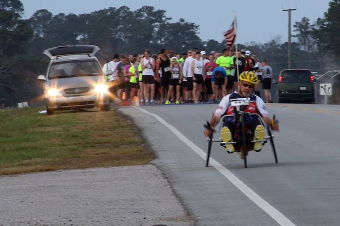 Paul Kelly, avid hand-cyclist, takes off from the starting line of the15th Annual Marine Corps Air Station Cherry Point Half Marathon March 22, 2014. Kelly, a retired electronics engineer with Naval Air Systems Command, started participating in various races and events in 2008 with the hopes of raising money and awareness for wounded service members.
