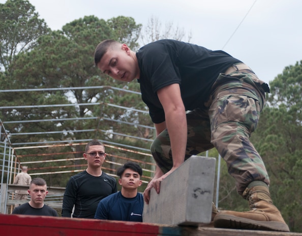 Raymond Lessig, a Notasulga Ala., native maneuvers a plank onto the platform of an obstacle during the Leader Ship Reaction Course here , March 22,2014. Lessig in one of more than 400 officer candidates from across the Southeastern United States that participated in a three-day mini Officer