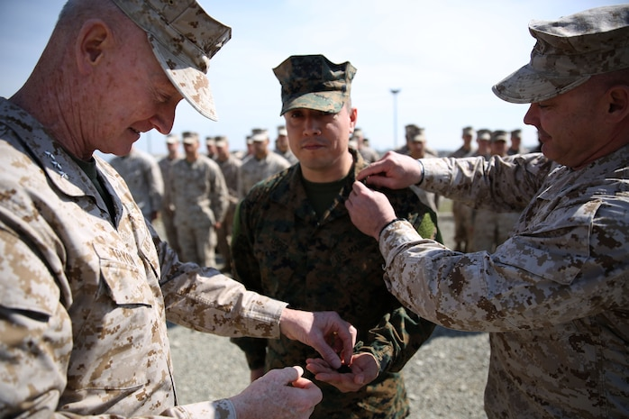 Lieutenant Gen. Richard Tryon, commander of U.S. Marine Corps Forces Command and U.S. Marine Corps Forces, Europe, and Master Gunnery Sgt. Troy Allen, the senior enlistment advisor of the Georgian Training Team pin the rank of master sergeant onto Master Sgt. Mario Lopez-Diaz, the senior enlisted advisor of Georgian Liaison Team 12, during his frocking ceremony March 20, 2014 aboard the Krstanisi National Training Center in Georgia. Georgian Liaison Team 12 is slated to deploy to Afghanistan as part of the International Security Assistance Force. Lopez-Diaz was frocked, which means he will wear the rank of master sergeant to fulfill his job position's requirements, but will not receive any pay increase until he officially is promoted. (Official Marine Corps photo by Lance Cpl. Scott W. Whiting, BSRF PAO/ Released)