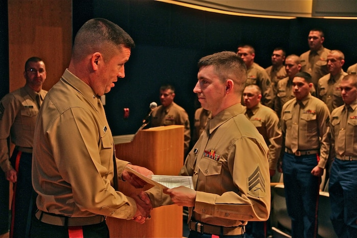 Brig. Gen. James Bierman, Commanding General, Marine Corps Recruit Depot, San Diego and Western Recruiting Region, presents Sgt. Matthew Kitsch, MEPS liaison, Recruiting Station Lansing, with a Meritorious Mast in Lansing, Mich. March, 25. Kitsch was recognized for his performance as a new liaison, in the absence of his supervisor, during five ship weeks in the months of January and February 2014.