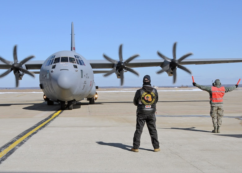 A member of the 143d Maintenance Group marshalls in a C-130J Super Hercules carrying members of the 143d Airlift Wing returning from a deployment to Kuwait in support of Operation Enduring Freedom while a member of the Combat Veterans Motorcycle Association looks on. National Guard Photo by Master Sgt Janeen Miller (RELEASED)