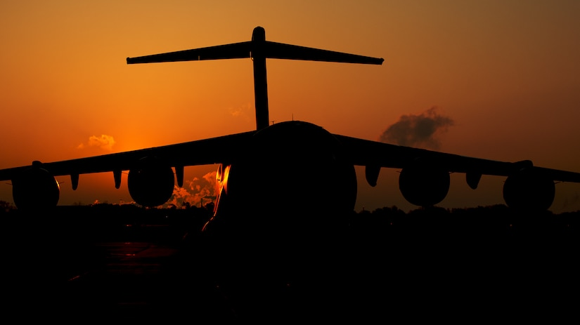 The sun rises above a C-17 Globemaster III assigned to the 437th Airlift Wing March 24, 2014, at Joint Base Charleston, S.C. The first C-17 to enter the Air Force's inventory arrived at Charleston Air Force Base in June 1993. The C-17 is capable of rapid strategic delivery of troops and all types of cargo to main operating bases or directly to forward bases in the deployment area. (U.S. Air Force photo/Senior Airman Dennis Sloan)