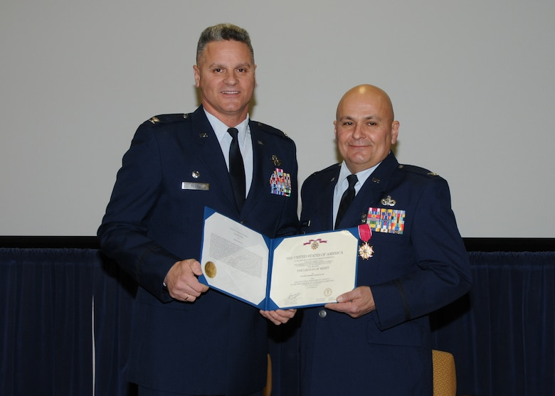 Colonel Arthur Floru (right), 143d Airlift Wing Commander, presents Colonel Robert Germani Jr. (left), outgoing 143d Airlift Wing Vice Commander with the Legion of Merit upon his retirement after 34 years of dedicated service to the Rhode Island National Guard. National Guard Photo by Technical Sgt Jason Long (RELEASED)