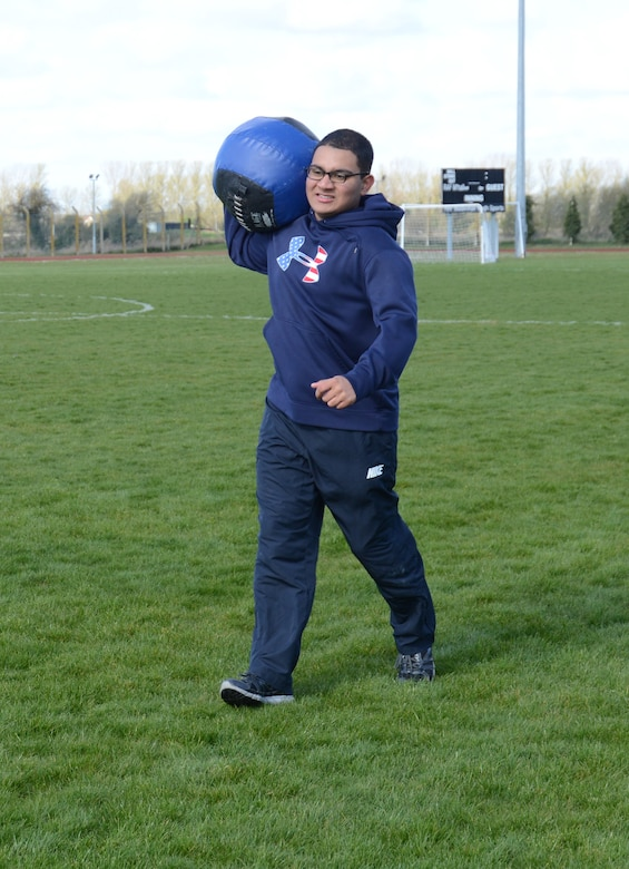 U.S. Air Force Airman 1st Class Carlos Ferran-Vargas, 100th Force Support Squadron fitness specialist from Colorado Springs, Colo., carries a medicine ball during a group event in a weight-loss competition March 22, 2014, on RAF Mildenhall, England. The event included running, speed walking, a sled pull and a medicine-ball carry. The group-event competition was worth a total of 10 points: four points for winning the competition, one for having the fastest walker and one point to each of the five teams that participated. The points will be added to the teams' final scores during the final weigh-in March 28. (U.S. Air Force photo by Airman 1st Class Kelsey Waters/Released)