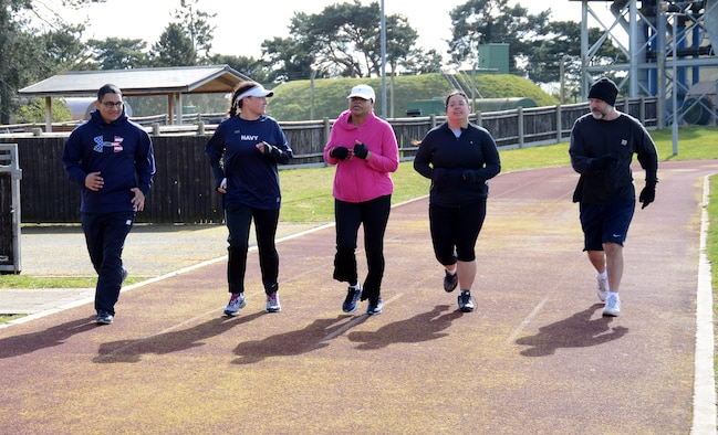 Members of the Black Team run together in the final event in a weight-loss group competition March 22, 2014, on RAF Mildenhall, England. The Team that wins each event receives points toward its overal score. The final weigh-in is scheduled to take place March 28. (U.S. Air Force photo by Airman 1st Class Kelsey Waters/Released)