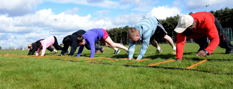 Members of the Purple Team perform an exercise during a weight-loss competition March 22, 2014, on RAF Mildenhall, England. The competition began Feb. 3, and is scheduled to end March 28. The competition will recognize an individual winner for the most weight lost and a team winner for the most points accumulated. (U.S. Air Force photo by Airman 1st Class Kelsey Waters/Released)