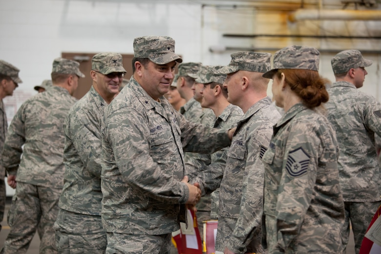 Brig. Gen. Gary W. Keefe, Massachusetts Air National Guard Commander, shakes hands with members of the 212th Engineering Installation Squadron and their families at Otis Air National Guard Base, Mass. on March 21, 2014. Members of the 212th will be deploying in support of Operation Enduring Freedom from late March to late November. (National Guard photo by Staff Sgt Jeremy Bowcock/Released)