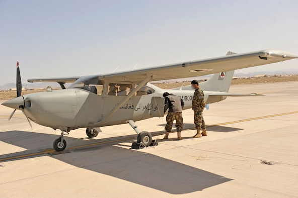 Two Afghan pilot students do a preflight check on a Cessna 182 at Shindand Airfield, Afghanistan, March 9, 2014. U.S. military advisors are training Afghan military members to fly and maintain aircraft at Shindand.(U.S. Air Force photo by Senior Master Sgt. Gary J. Rihn) (Faces blurred for security purposes)