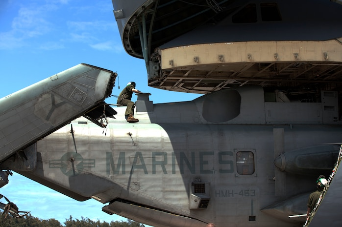 A Marine with Marine Heavy Helicopter Squadron 463 sits on top of a CH-53E Super Stallion helicopter as it is loaded onto a U.S. Air Force C-5 Galaxy at Marine Corps Air Station Kaneohe Bay here March 23. HMH-463 is a part of the Aviation Combat Element deploying to Australia for this iteration of Marine Rotational Force – Darwin.