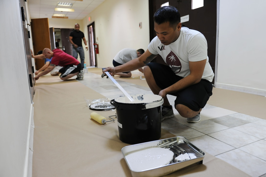 Airmen from the 728th Air Mobility Squadron and Airmen enrolled in Airman Leadership School class 14-3 paint the hallways and classrooms in the ALS schoolhouse March 22, 2014, Incirlik Air Base, Turkey.  Each ALS class participates in one community activity and leaves behind one legacy project while enrolled in the course. (U.S. Air Force photo by Senior Airman Nicole Sikorski/Released)