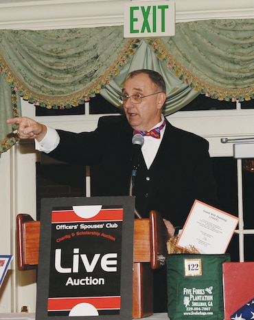 Kent Morrison, Marine Corps Logistics Base Albany's executive director, acts as the auctioneer for the Officers Spouses' Club auction, Feb. 15, at the Doublegate Country Club in Albany, Ga.