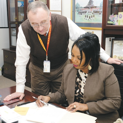 Kent Morrison, Marine Corps Logistics Base Albany's executive director, reviews documents with Laura A. Thorne, executive assistant to the commanding officer, Marine Corps Logistics Base Albany, recently.