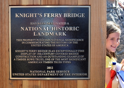 Violet Tande, daughter of Lt. Col. Chris Tande, a contracting team leader with the U.S. Army Corps of Engineers Sacramento District, helps unveil the National Historic Landmark plaque for the Knights Ferry covered bridge at the Corps' Stanislaus River Parks in Knights Ferry, Calif., March 22, 2014.