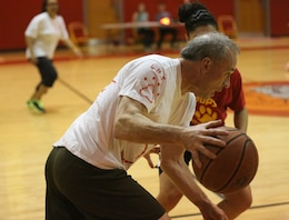 Jeff Carr, a member of the staff team, maneuvers around an opponent during the Lejeune March Madness basketball competition at Lejeune High School, March 21. Carr and the staff team played their way to victory.
