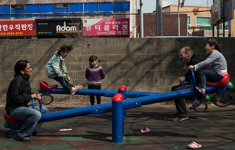 Tech. Sgt. Saara Mustapha, 51st Fighter Wing noncommissioned officer in charge of executive services, and Staff Sgt. Logan Pendragon, a 51st Comptroller Squadron relocations technician, both from Osan Air Base, Republic of Korea, play with children on the see-saw March 22, 2014, at the Aehyang Child Welfare Center in Pyeongtaek. Airmen from Osan AB routinely volunteer at the orphanage to establish a bond between the base and its local community. (U.S. Air Force photo by Staff Sgt. Jake Barreiro)