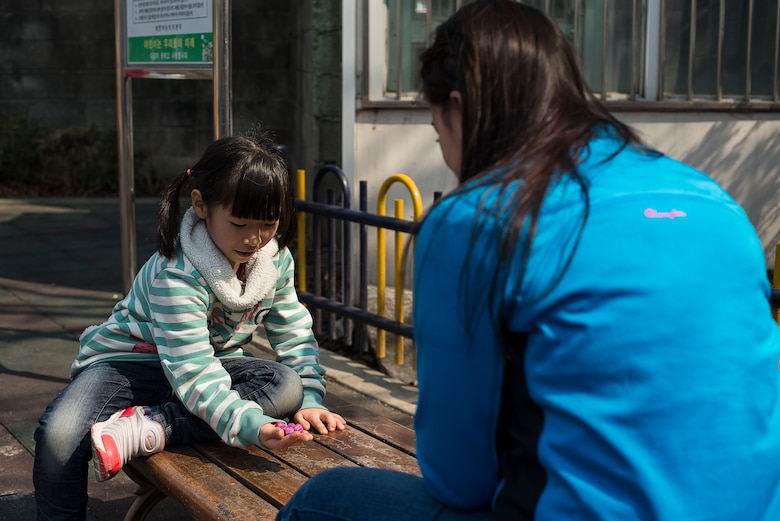 Senior Airman Kayla Ciriello, a 51st Comptroller Squadron relocations technician at Osan Air Base, Republic of Korea, plays gonggi with a child March 22, 2014, at the Aehyang Child Welfare Center in Pyeongtaek. Gonggi is a popular children's game in Korea, and the orphans taught the Airmen how to play. (U.S. Air Force photo by Staff Sgt. Jake Barreiro)