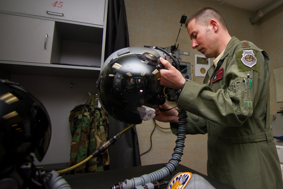 U.S. Air Force Maj. Jason Halvorsen inspects his helmet with the Helmet Mounted Integrated Targeting system installed at the aircrew flight equipment shop of the New Jersey Air National Guard's 177th Fighter Wing on March 25, 2014. The HMIT is a force multiplier, with a cueing system that allows rapid target acquisition, giving aircrew the ability to acquire targets by looking at them. HMIT is also compatible with existing night vision devices, and supports night operations while retaining full color displays via a high resolution device in front of the pilot's eye. The display technology allows pilots to place data-linked symbology over enemy targets and friendly positions.  Halvorsen is an F-16 Fighting Falcon pilot from the 119th Fighter Squadron. (U.S. Air National Guard photo by Tech. Sgt. Matt Hecht/Released)