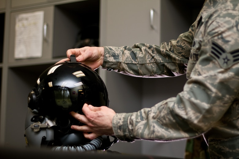 U.S. Air Force Senior Airman Eric Halladay inspects an F-16 Fighting Falcon pilot's helmet with the Helmet Mounted Integrated Targeting (HMIT) system installed in the aircrew flight equipment shop of the New Jersey Air National Guard's 177th Fighter Wing,  March 25, 2014. The HMIT is a force multiplier, with a cueing system that allows rapid target acquisition, giving aircrew the ability to acquire targets by looking at them. HMIT is also compatible with existing night vision devices, and supports night operations while retaining full color displays via a high resolution device in front of the pilot's eye.  Halladay is an Aircrew Flight Equipment specialist with the 177th Fighter Wing, and is from Carteret, N.J.  (U.S. Air National Guard photo by Tech. Sgt. Matt Hecht/Released)