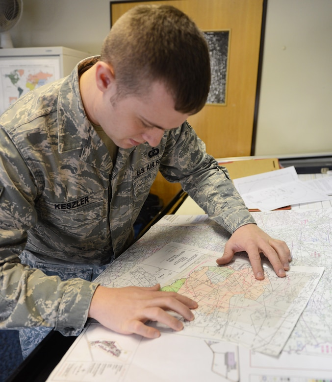 Staff Sgt. Kevin M. Keszler, international terminal and en-route procedures specialist, reviews a map overlay against an airspace map to make a minimum vectoring altitude chart at Ramstein Air Base, Germany March 3, 2014. Keszler works in the Air Base Support Terminal Procedures Section of the U.S. Air Forces in Europe and Air Forces Africa Air Procedures Flight. He's responsible for maintaining instrument flight procedures for 17 bases.  (U.S. Air Force photo/Tech. Sgt. James M. Hodgman)