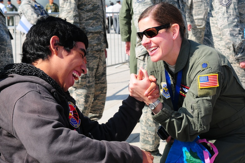 Lt. Col. Kat Callaghan, the 571st Mobility Support Advisory Squadron director of operations, spends time with a Chilean boy from the Telet?n Foundation at the FIDAE Air Show in Santiago, Chile, March 26. Nearly 60 U.S. airmen are participating in subject matter expert exchanges with Chilean air force counterparts during FIDAE, and as part of the events are hosting static displays of the C-130 Hercules and F-16. Airmen from the Texas Air National Guard set aside time to host the children before the public days of FIDAE, which are scheduled for the weekend. (U.S. Air Force photo by Senior Master Sgt. Miguel Arellano/Released)