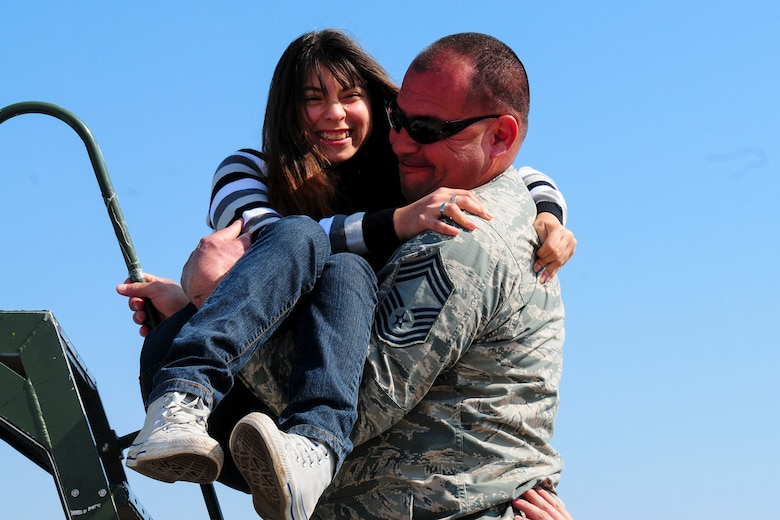 Chief Master Sgt. Caesar Acosta, an aircraft maintenance specialist for the Texas Air National Guard, carries a wheelchair-bound Chilean girl up stairs to look inside the cockpit of a U.S. F-16 Fighting Falcon at the FIDAE Air Show in Santiago, Chile, March 26.  Nearly 60 U.S. airmen are participating in subject matter expert exchanges with Chilean air force counterparts during FIDAE, and as part of the events are hosting static displays of the C-130 Hercules and F-16.  Airmen from the Texas Air National Guard set aside time to host the children before the public days of FIDAE, which are scheduled for the weekend. (U.S. Air Force photo by Senior Master Sgt. Miguel Arellano/Released)