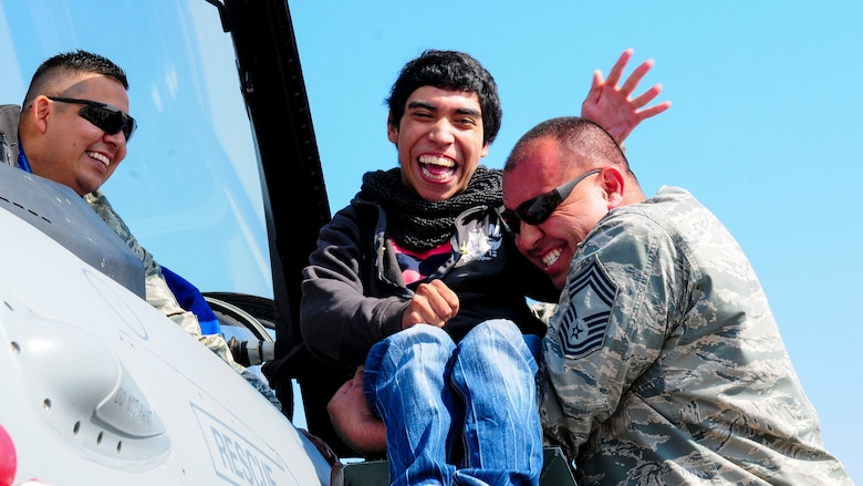 Chief Master Sgt. Caesar Acosta, an aircraft maintenance specialist for the Texas Air National Guard, carries a wheelchair-bound Chilean boy up stairs to look inside the cockpit of a U.S. F-16 Fighting Falcon at the FIDAE Air Show in Santiago, Chile, March 26. Nearly 60 U.S. airmen are participating in subject matter expert exchanges with Chilean air force counterparts during FIDAE, and as part of the events are hosting static displays of the C-130 Hercules and F-16. Airmen from the Texas Air National Guard set aside time to host the children before the public days of FIDAE, which are scheduled for the weekend. (U.S. Air Force photo by Senior Master Sgt. Miguel Arellano/Released)