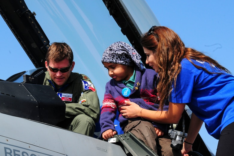 Maj. Steve Fargo, a fighter pilot for the Texas Air National Guard, shows off the F-16 Fighting Falcon to a girl from the Make-A-Wish Foundation at the FIDAE Air Show in Santiago, Chile, March 26. Nearly 60 U.S. airmen are participating in subject matter expert exchanges with Chilean air force counterparts during FIDAE, and as part of the events are hosting static displays of the C-130 Hercules and F-16. Airmen from the Texas Air National Guard set aside time to host the children before the public days of FIDAE, which are scheduled for the weekend. (U.S. Air Force photo by Senior Master Sgt. Miguel Arellano/Released)
