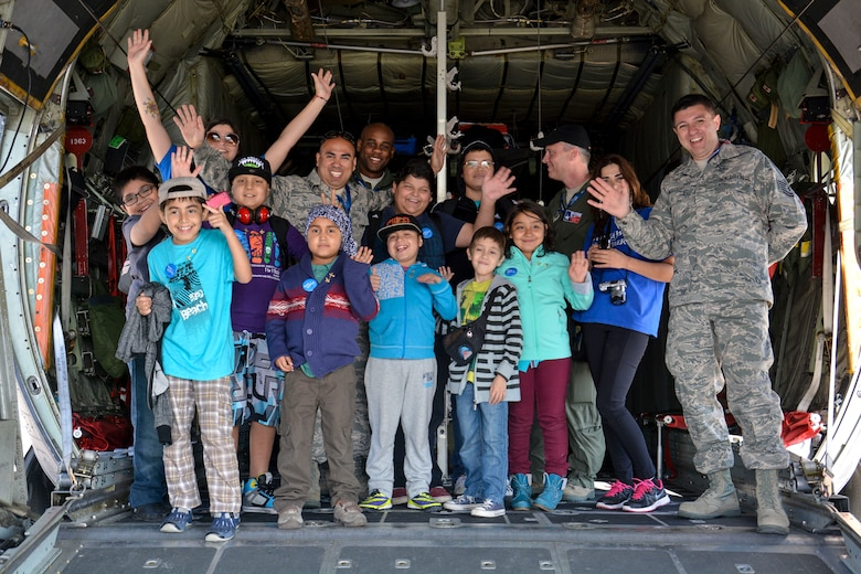 Airmen from the Texas Air National Guard pose for a photo on the ramp of a U.S. C-130 Hercules with Chilean children from the Make-A-Wish and Telet?n Foundations at the FIDAE Air Show in Santiago, Chile, March 26. Nearly 60 U.S. airmen are participating in subject matter expert exchanges with Chilean air force counterparts during FIDAE, and as part of the events are hosting static displays of the C-130 and F-16 Fighting Falcon. Airmen from the Texas Air National Guard set aside time to host the children before the public days of FIDAE, which are scheduled for the weekend. (U.S. Air Force photo by Capt. Justin Brockhoff/Released)