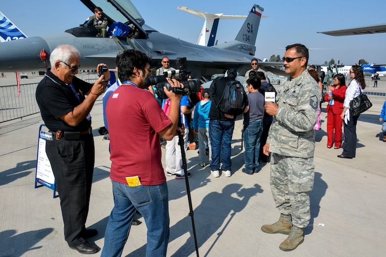 Master Sgt. Pablo Soriano, an aircraft maintenance specialist from the Texas Air National Guard, speaks with the media while children from the Make-A-Wish and Telet?n Foundations tour U.S. aircraft at the FIDAE Air Show in Santiago, Chile, March 26. Nearly 60 U.S. airmen are participating in subject matter expert exchanges with Chilean air force counterparts during FIDAE, and as part of the events are hosting static displays of the C-130 Hercules and F-16 Fighting Falcon. Airmen from the Texas Air National Guard set aside time to host the children before the public days of FIDAE, which are scheduled for the weekend. (U.S. Air Force photo by Capt. Justin Brockhoff/Released)