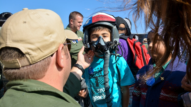 Lt. Col. Greg Pohoski (far left), a fighter pilot assigned to the Texas Air National Guard, helps a Chilean boy from the Make-A-Wish Foundation try on a helmet and oxygen mask at the FIDAE Air Show in Santiago, Chile, March 26. Nearly 60 U.S. airmen are participating in subject matter expert exchanges with Chilean air force counterparts during FIDAE, and as part of the events are hosting static displays of the C-130 Hercules and F-16 Fighting Falcon. Airmen from the Texas Air National Guard set aside time to host the children before the public days of FIDAE, which are scheduled for the weekend. (U.S. Air Force photo by Capt. Justin Brockhoff/Released)