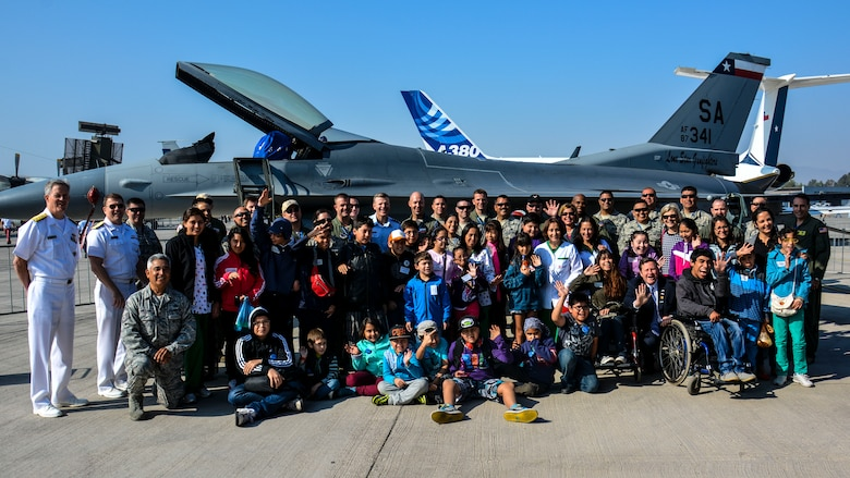 Personnel from the U.S. Air Force, U.S. Navy and U.S. Embassy, pose for a photo in front of a U.S. F-16 Fighting Falcon with Chilean children from the Make-A-Wish and Telet?n Foundations at the FIDAE Air Show in Santiago, Chile, March 26. Nearly 60 U.S. airmen are participating in subject matter expert exchanges with Chilean air force counterparts during FIDAE, and as part of the events are hosting static displays of the C-130 Hercules and F-16. Airmen from the Texas Air National Guard set aside time to host the children before the public days of FIDAE, which are scheduled for the weekend. (U.S. Air Force photo by Capt. Justin Brockhoff/Released)