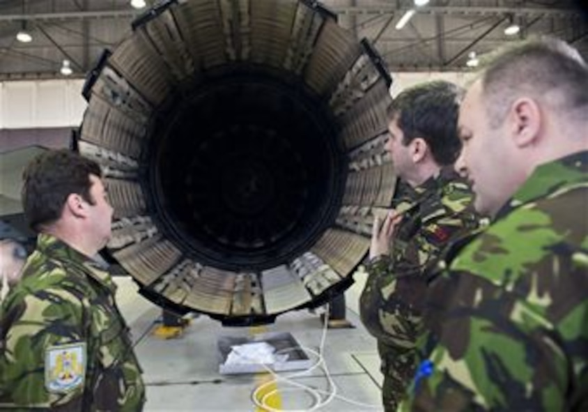 Romanian air force members examine the engine exhaust nozzle of an F-16 Fighting Falcon fighter aircraft during a familiarization tour at Spangdahlem Air Base, Germany, March 25, 2014. The purpose of the visit was for Romanian air force officials to observe the structure and operation of an F-16 squadron before laying the framework for their transition from the MiG-21 fighter aircraft. (U.S. Air Force photo by Staff Sgt. Chad Warren/Released)