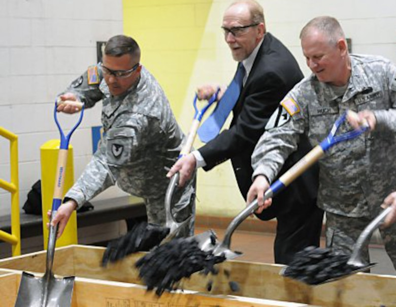 Col. David J. Luders, left, commander Rock Island Arsenal Joint Manufacturing and Technology Center; Congressman Dave Loebsack, who represents Iowa's second congressional district and Col. Robert Ruch, commander, Huntsville Center, remove excess coal from the factory's supply to symbolize energy savings to be realized in the Rock Island Arsenal JMTC Plating shop as a result of the changes made during the Energy Savings Performance Contract during a ceremony at Rock Island Arsenal.