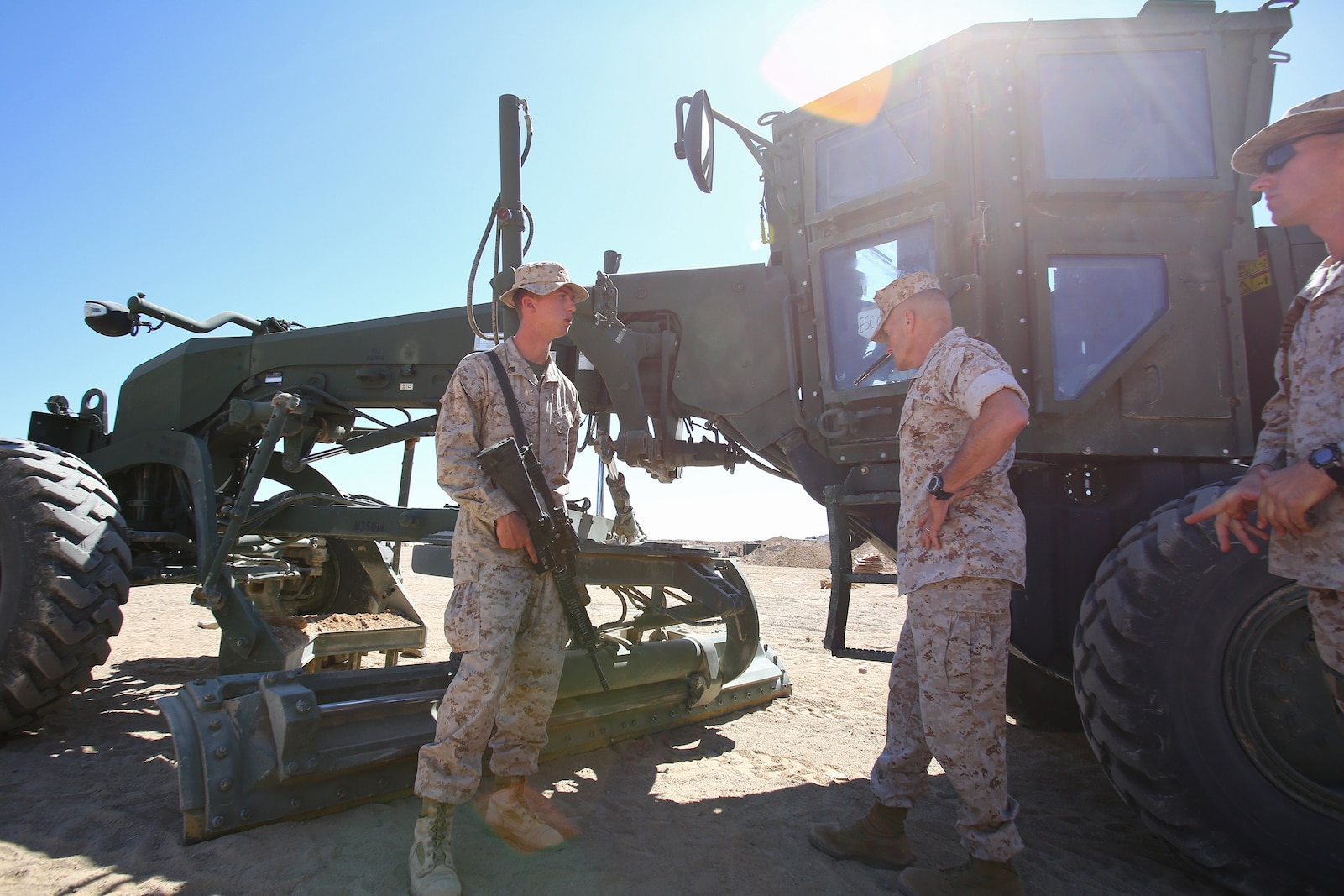Brigadier Gen. Vincent A. Coglianese (right), commanding general, 1st Marine Logistics Group, talks with Cpl. Jacob R.  Pierce, heavy equipment operator, Combat Logistics Battalion 1, Combat Logistics Regiment 1, 1st MLG, when Pierce described the 120M military motor grader during Integrated Training Exercise 3-14 aboard Marine Corps Air Ground Combat Center Twenty-nine Palms, Calif., March 21, 2014. The month-long ITX prepares the battalion for its role, as the logistics combat element, in the final combat deployment of Operation Enduring Freedom. Pierce, 21, is from San  Antonio, Texas.