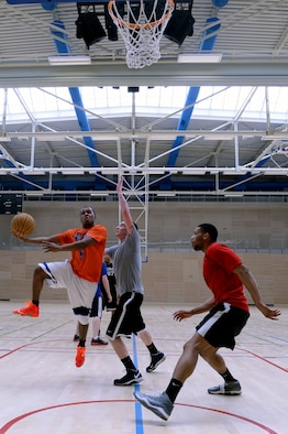 Senior Airman Gregory Haynes, 52nd Logistics Readiness Squadron, attempts a layup during a First IV-sponsored March Madness basketball tournament at the Eifel Powerhaus at Spangdahlem Air Base, Germany, March 27, 2014. The tournament included eight teams of three participants, one of which had to be an Airman. (U.S. Air Force photo by Senior Airman Alexis Siekert/Released)