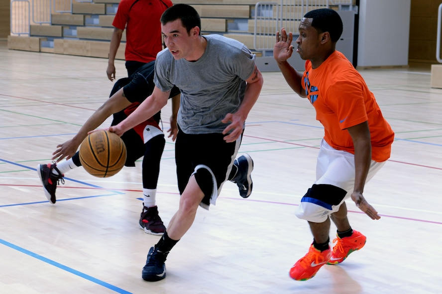 Airman 1st Class Christopher Ray, 52nd Logistics Readiness Squadron, drives to the basket past Senior Airman Gregory Haynes, 52nd Logistics Readiness Squadron, during a basketball tournament at the Eifel Powerhaus at Spangdahlem Air Base, Germany, March 27, 2014. This free event was organized by the First IV Airman's Council as a fun way to get people active. (U.S. Air Force photo by Senior Airman Alexis Siekert/Released)