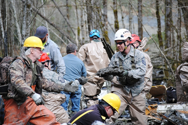 Washington Air National Guardsmen methodically make their way through the mud and wreckage left behind by Saturday's mudslide in Oso, Wash. More than 70 guardsmen have been activated to support the search and rescue efforts. (Photo by Spc. Matthew Sissel, 122D PAOC)