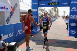 Jan Frodeno and Andy Potts shake hands after finishing the IRONMAN 70.3 California Oceanside race on March 29, 2014. Frodeno is an Olympic gold medalist and Potts is a five-time IRONMAN champion. The IRONMAN 70.3 is a 1.2-mile swim transitioning into a 56-mile bike ride followed by a 13.1-mile run to the finish line. The race draws competitors from all over the world. The course starts in Oceanside Harbor and follows the coast making its way to northern Camp Pendleton before looping southward through the base back to the Oceanside Pier area and the finish line. This year's men's champion was Jan Frodeno, a German native and an Olympic gold medalist, beating the defending champion American Andy Potts by only a few minutes. 