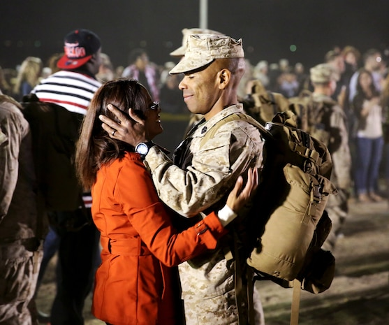 1st Sgt. Jairo Fredonis, weapons company first sergeant, 3rd Battalion, 7th Marine Regiment, embraces his wife, Monique Fredonis, during a homecoming at Del Valle Field, March 22, 2014. The homecoming welcomed Marines and sailors with 3/7, after a seven-month deployment to Afghanistan.