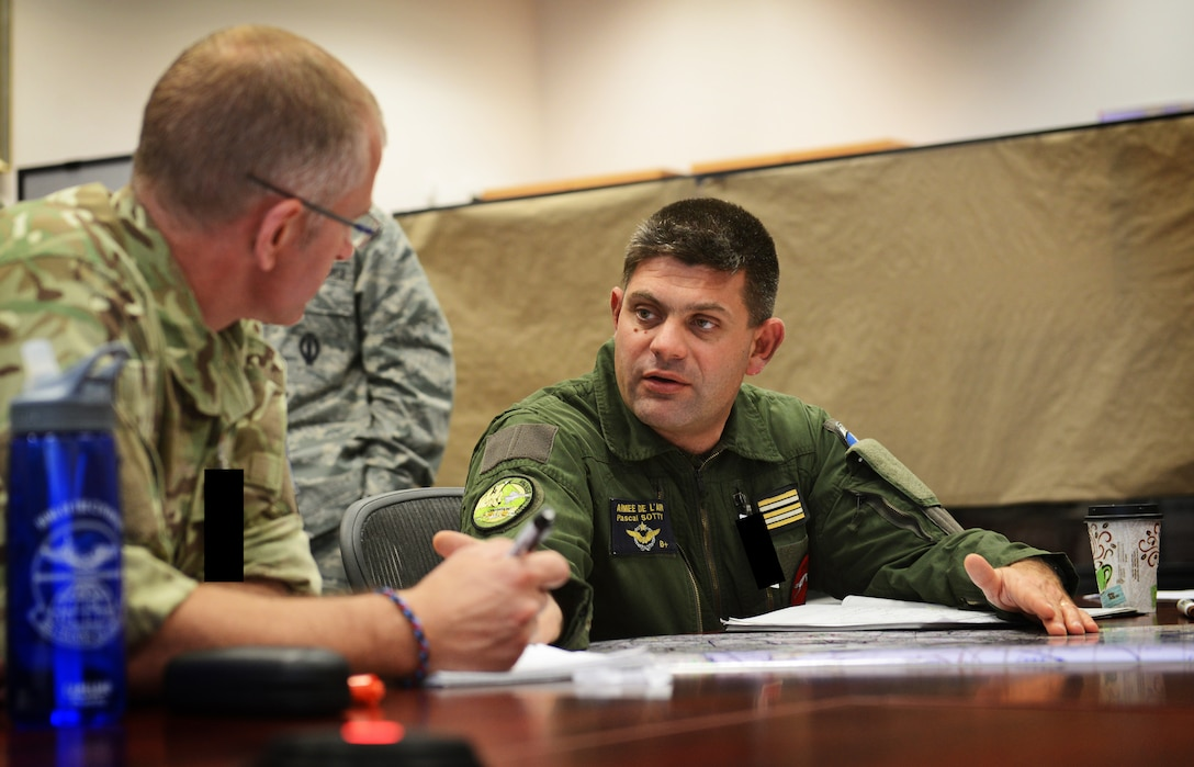 Squadron Leader Gordon Ferguson from the U.K. and LCL Pascal Sotty from France, plan the tri-lateral exercise, Tonnerre Lightning, with U.S. Air Force pilots and 603rd Air and Space Operations Center planning teams on March 27, 2014 at Ramstein Air Base, Germany. The exercise is the first in a series of semi-annual exercises between the NATO countries to improve interoperability and communication in the event of a real-world scenario. This first exercise was conducted off of the English coast and focused on strengthening communication between all agencies involved. (U.S. Air Force photo/Staff Sgt. Ryan Crane)