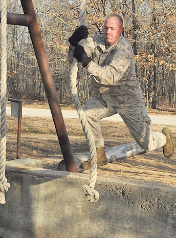 Marine Sgt. Michael Baldwin, Marine Corps Detachment, swings across a pit during the Physical Endurance Confidence course event.